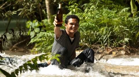 Ragazzo laotiano che alza la birra al cielo sorridendo
